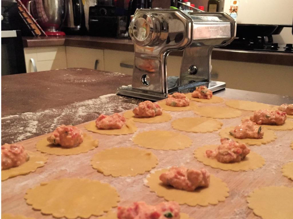 Machine à pâte, ravioles garnies + couvercle et cuisine en fond de tableau