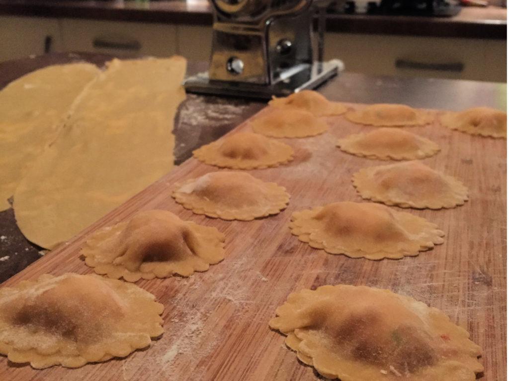machine à pâte, deux pâtons étalés en fond et des ravioles finies sur la planche